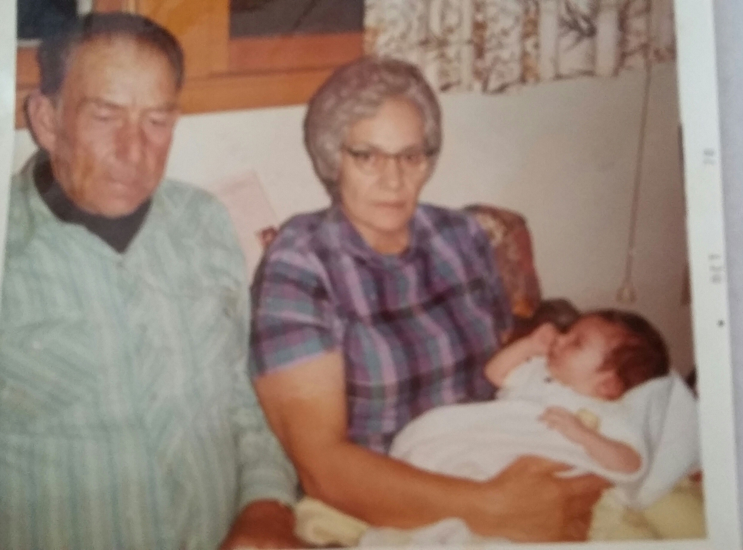 This is a picture of my Uncle Bud and Aunt Jo showing traditional Lakota generosity as they hold my firstborn son Clint.